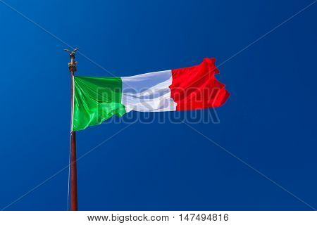 Italian flag fluttering in the wind on the flagpole with blue sky. Green White and Red are Italian national colors.