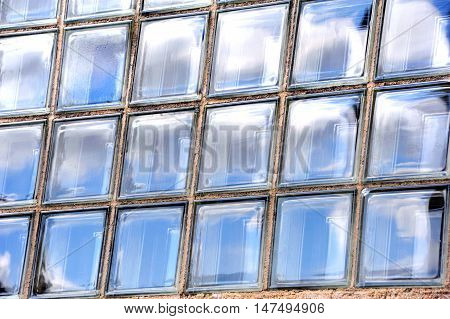 Background image shows sky reflected in rectangle panes of glass. Window is made of individual panes of thick glass.