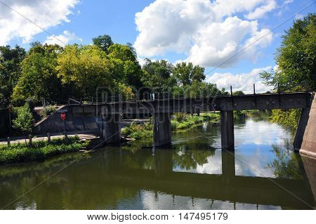 Yahara River flows beneath the train tracks along the Cooper Causeway in Stoughton Wisconsin.