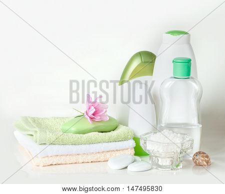 Green and white containers with different cosmetics soap and a stack of towels isolated on white background
