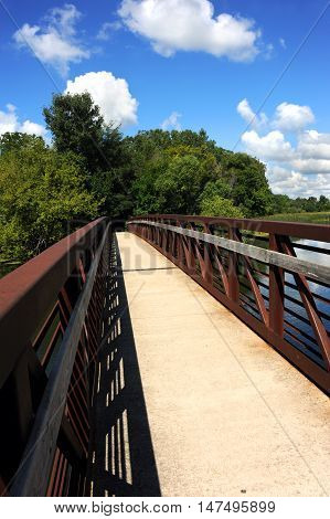 Steel and concrete bridge begins the Yahara River Trail in Stoughton Wisconsin. Bridge arches and then disappears in the distance.