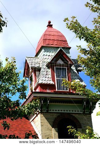 Beautiful Queen Ann Victorian home has a square tower topped with a four sided dome with four dormers. Wooden shingles are faded pastel green.