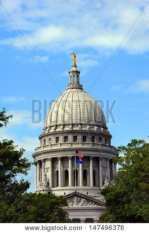 Capitol building of Wisconsin at Madison is surrounded by blue skies and trees. Flags fly in front of Capitol.