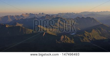 Mountain ranges in the Swiss Alps at sunrise. Lake Arnensee. View from Sex Rouge Glacier de Diablerets. Summer morning.