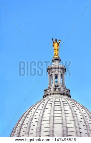 Cupola of the Capitol of Wisconsin in Madison is topped with golden figure. Blue sky surrounds roof.