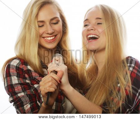 life style, happiness, emotional and people concept: two beauty girls with a microphone singing and having fun