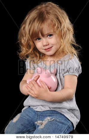 Young girl holding piggy bank isolated over a black background