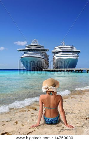 Woman relaxing on beach with cruise ships in background