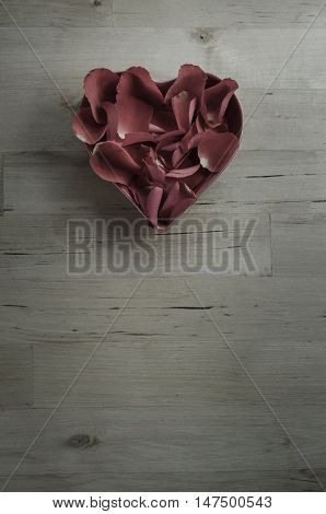 Plum Toned Rose Petals In Heart Shaped Bowl On Wood