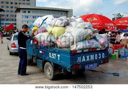 Pengzhou China - May 15 2008: Volunteer loads a truck with donations collected for the victims of the 8.2 earthquake in Sichuan Province on 12 May 2008