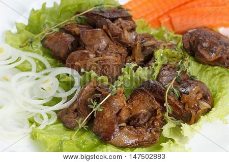 Appetizing chicken liver stewed with onions and spices lettuce and spices closeup