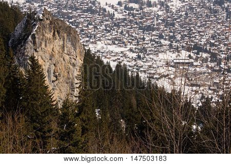 A cliff towers above the treetops on the outskirts of a town in the Swiss alps.