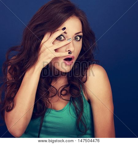 Fun Surprising Makeup Woman Covering Face The Manicured Fingers On Blue Background. Happy Funny Port