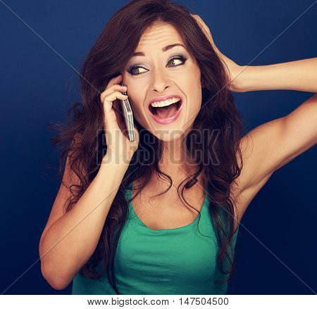 Beautiful Emotional Woman Talking On Mobile Phone And Loud Shouting With Opened Mouth On Blue Backgr