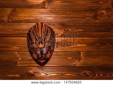 Traditional Indonesian mask Baliness on wooden background
