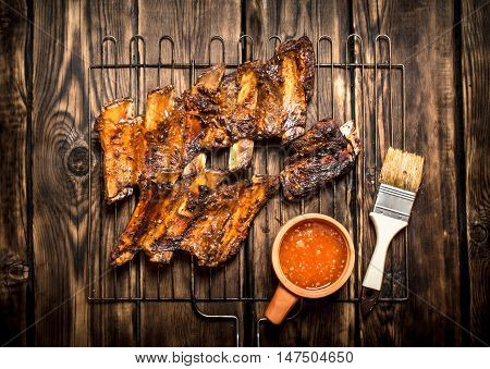 Fried pork ribs with tomato sauce. On a wooden table.