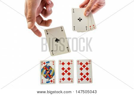 man holding gaming cards and trowing one agaisnt white four aces