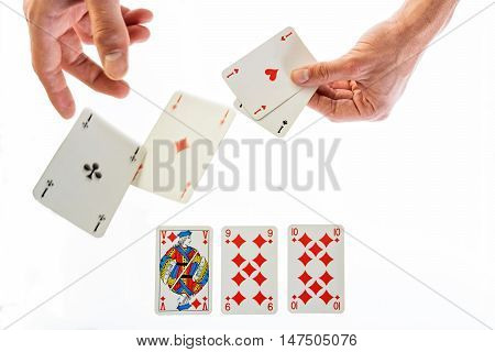 man holding gaming cards and trowing two agaisnt white four aces