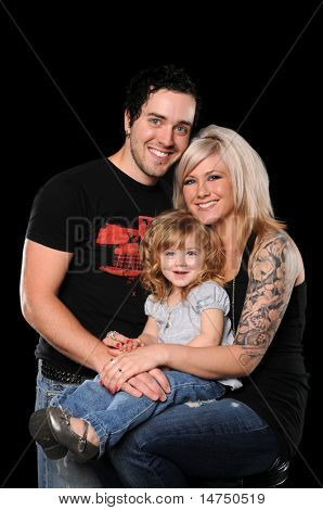 Young couple with daughter isolated over black background