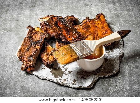 Pork ribs grilled with tomato sauce. On a stone background.
