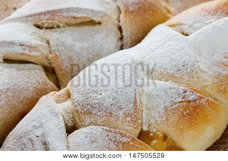 Ruddy roll is strewed by powdered sugar with a stuffing from apple jam