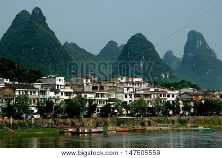 Yangshuo China - April 29 2006: Dramatic karst rock formations covered with trees rise above riverside houses on the banks of the Lijiang River