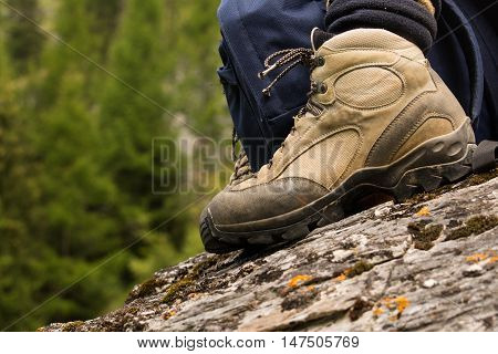 A brown hiking boot on a grey rock