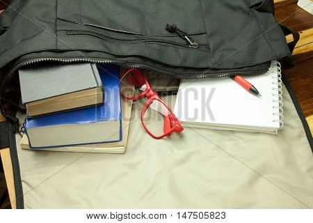 Top view of casual life style bag ; Old book,notebook,red glasses and casual shoes from inside bag.