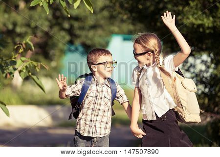 Smiling young school children in a school uniform runing in the park at the day time. Concept of the children are ready to go to school.