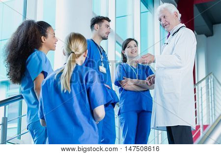 Group of medical interns talking to a senior doctor on a bright stairway