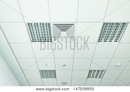 White office ceiling with lighting and ventilation equipment.
