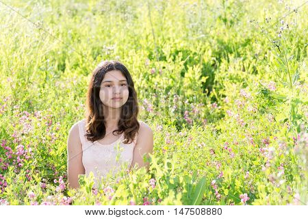 Modest well-groomed girl on the summer flower meadow