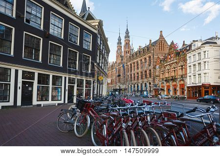 Amsterdam Netherlands - July 03 2016: Bicycle parking on the background of shopping centre Magna Plaza morning time