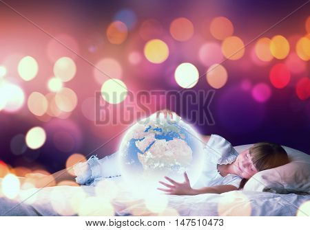 Cute girl in bed looking at glowing Earth planet. Elements of this image are furnished by NASA