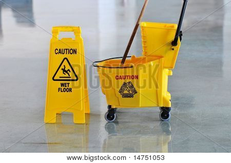 Mop bucket and caution sign on wet floor