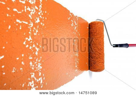 Pain roller with orange paint on white wall