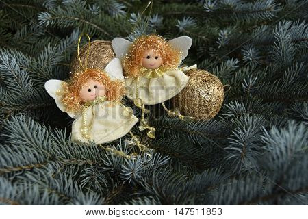 Christmas toys in the form of angels and a sphere. Toys are located on a fir-tree. Angels in white clothes. Sphere of gold color