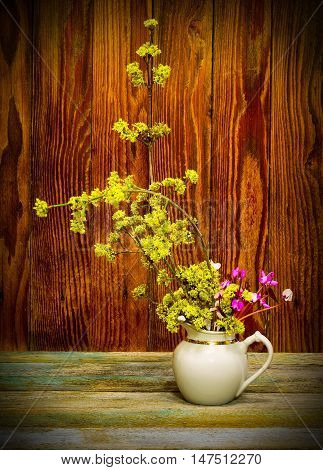 blooming twig dogwood and cyclamen flowers in a white jug. picture with vignette