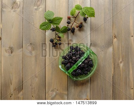 Top down image of a vintage green glass basket full of juicy blackberries with two sprigs of blackberries and leaves