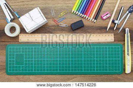 Business concept:stapler,glue,scissor,cutter,tape,pen,pencil,clip,ruler,rubber, cutting mat,divider,sharpener,wooden block calendar and color pencil on wooden
