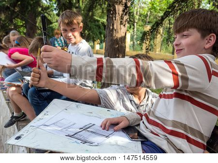 Alushta, Russia - June 09, 2016: Young artist determines the proportions with a pencil
