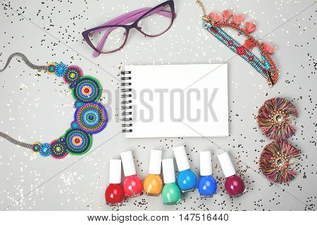 Beautiful multicolored frame made of woman accessories and rainbow of nail polishes. All stuff is lying on grey festive background. Place for your text.