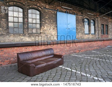 A sofa dumped in abandoned industrial backyard. Concept: economic crisis and unemployment