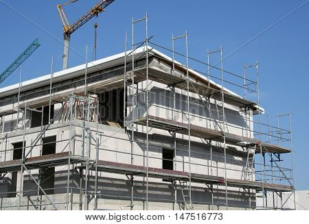 Residential house under construction with scaffolding and cranes in Germany 2008