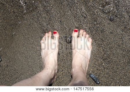 barefoot feet with lacquered nails in the sand