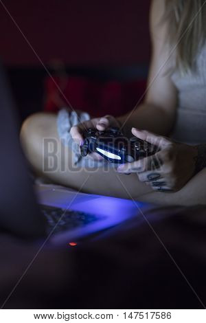 Gothenburg, Sweden - September 16, 2016: A shot at night of a young womans hands holding a video game controller for the Playstation 4, developed by Sony. She is sitting in bed in front of her laptop.