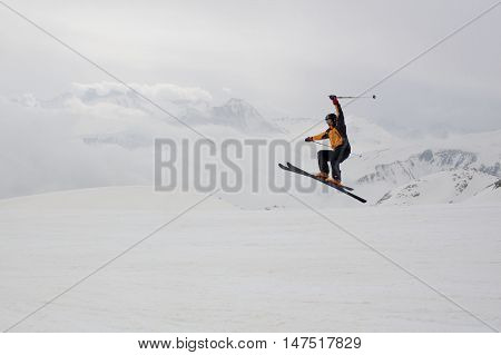 Skier Jumping With A Range Mountain Background