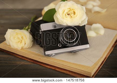 Vintage camera and beautiful roses on open photo album