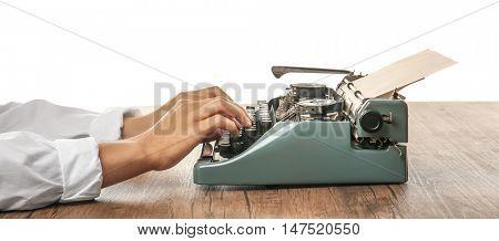 Man working on retro typewriter at desk on white background