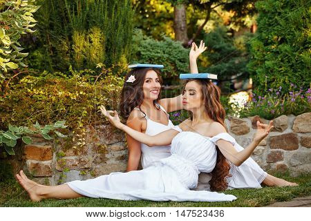 Two cute sisters fooling around with books sitting on the lawn. The girls put books on their heads. They represent themselves Greek nymphs.